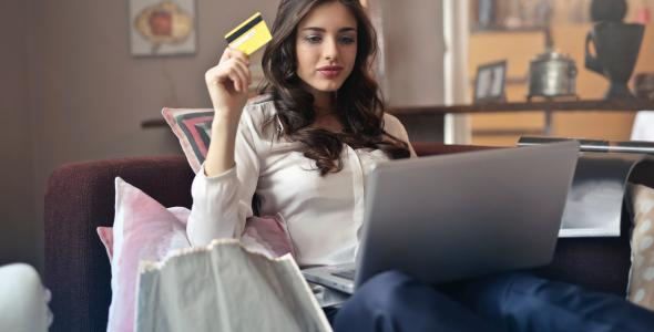 Young woman on laptop holding bank card